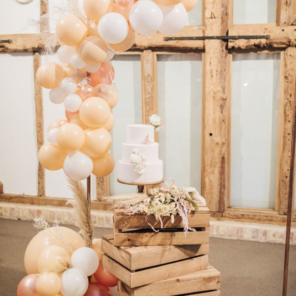 Natual barn wedding - wedding cake and balloon arch